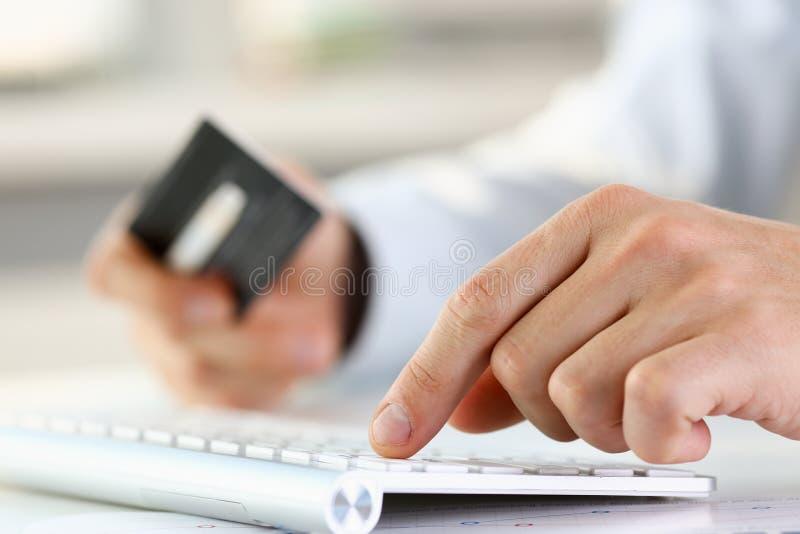 Мужские оружия держат кнопки прессы кредитной карточки стоковые изображения rf