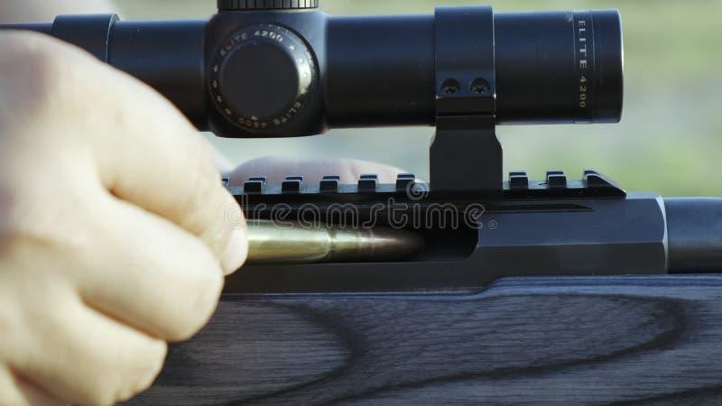 Мужские пальцы нагружают винтовку патрона по-одному стоковое фото