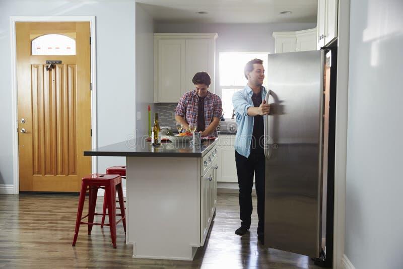 Мужские пары в кухне подготавливая еду, раскрывая холодильник стоковые изображения rf