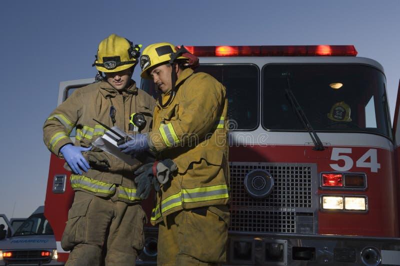 Мужские пожарные читая документ стоковые изображения rf