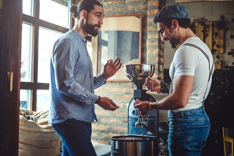 Мужские предприниматели смотря кофейное зерно roaster кофе стоковые фотографии rf