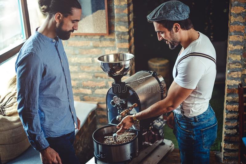 Мужские предприниматели смотря машину roaster кофе стоковая фотография rf