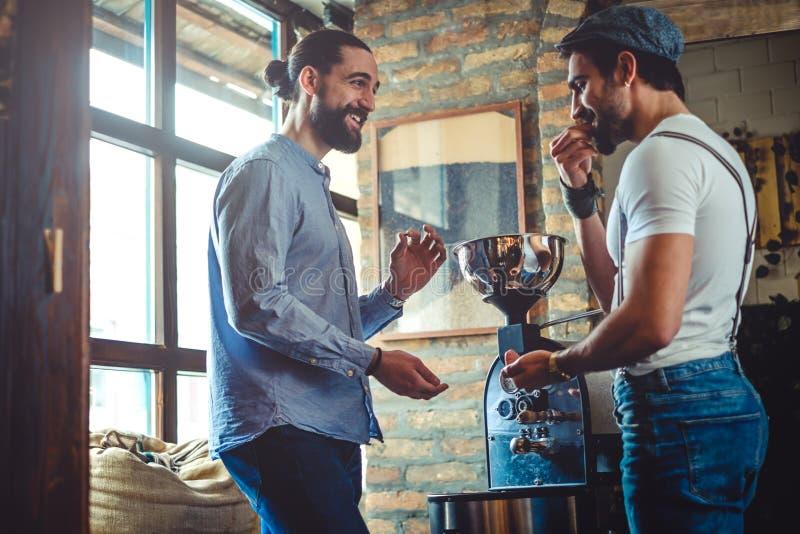 Мужские предприниматели усмехаясь пока пробующ кофейное зерно roaster стоковая фотография rf