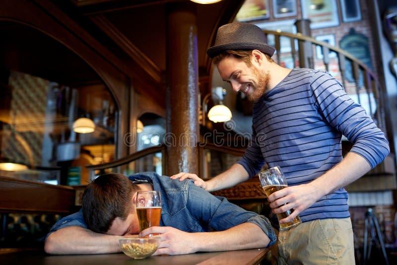 Мужские друзья выпивая пиво на баре или пабе стоковое фото rf