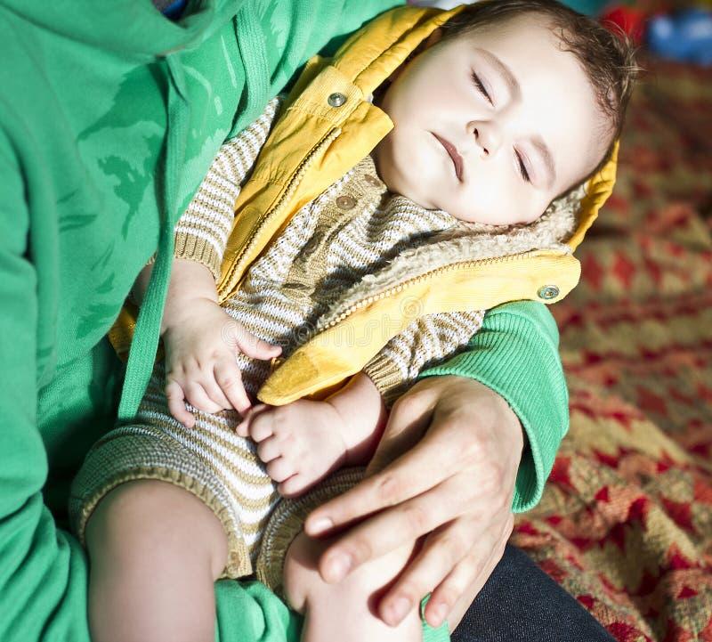 Мужские руки держат спать ребенка стоковая фотография