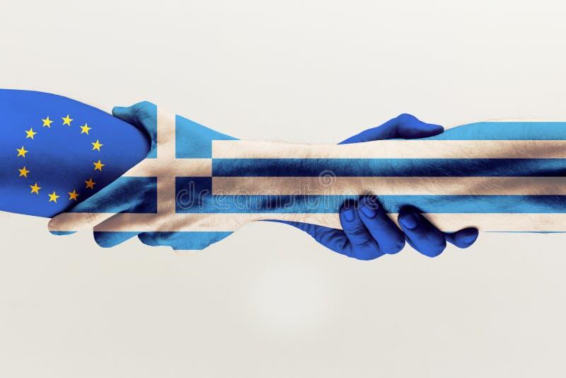 Мужские руки держа покрашенными в голубом флаге ЕС и Греции стоковая фотография