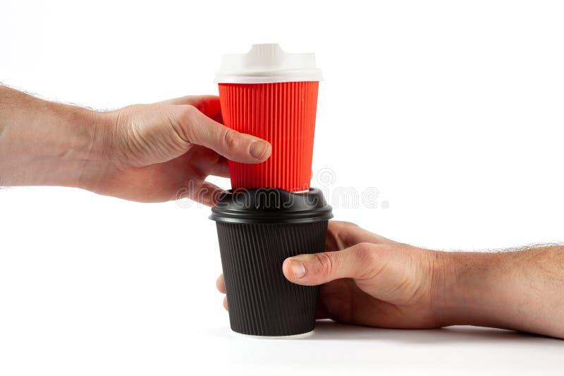 Мужские руки держа штабелированные пластичные кофейные чашки стоковые изображения