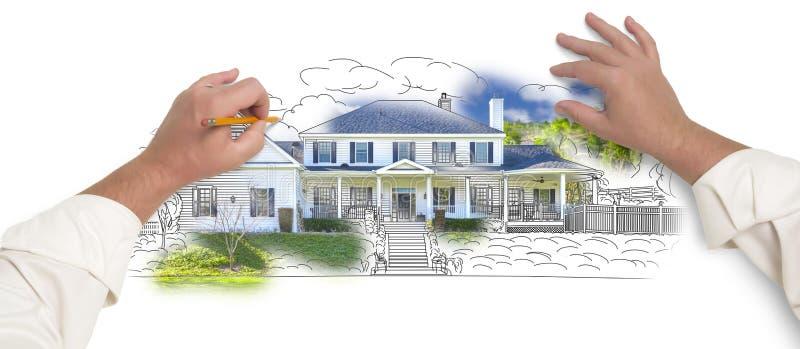 Мужские руки делая эскиз к дому при фото показывая до конца стоковое изображение rf