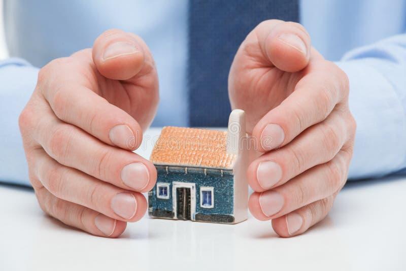 Мужские руки защищают дом игрушки стоковое фото