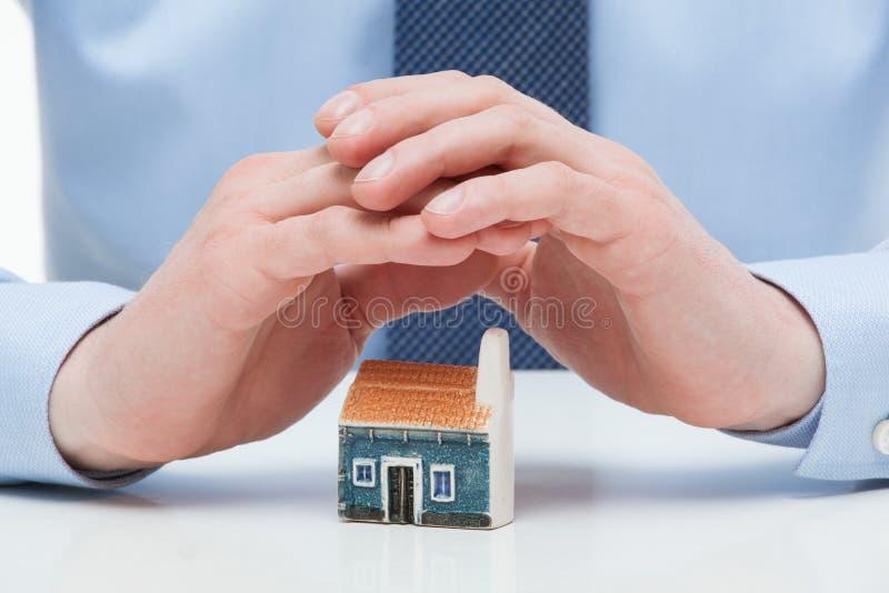 Мужские руки защищают дом игрушки стоковое изображение