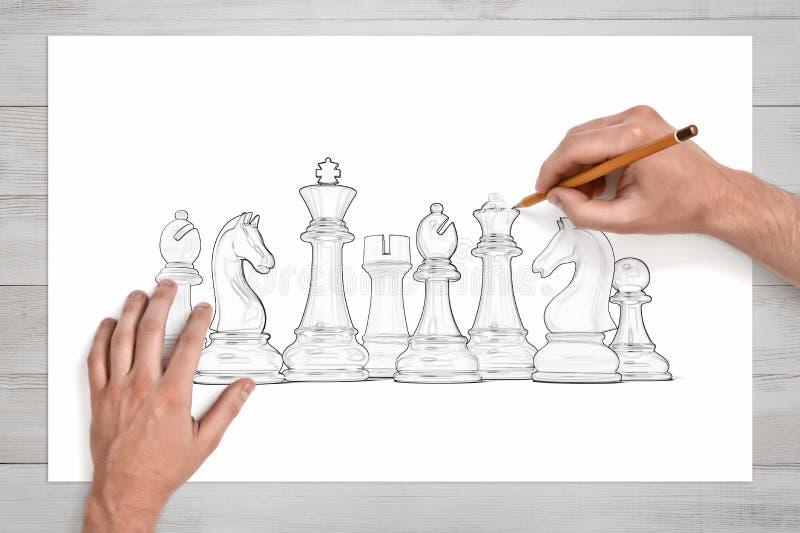 Мужские руки используют карандаш для того чтобы нарисовать полный комплект белых шахматных фигур на бумаге стоковые фотографии rf