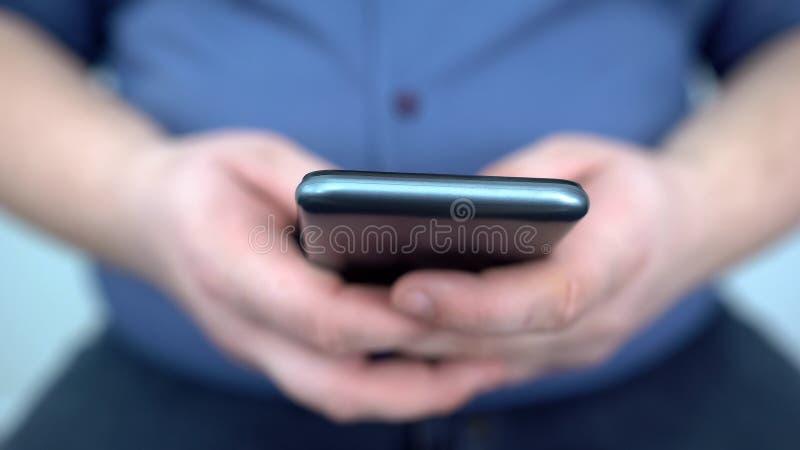 Мужские руки используя конец смартфона вверх, ищущ применения диеты, наркомания стоковые изображения
