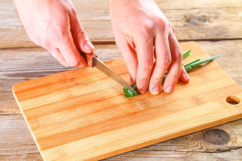 Мужские руки отрезали зеленый лук на разделочной доске на старом деревянном столе стоковое изображение