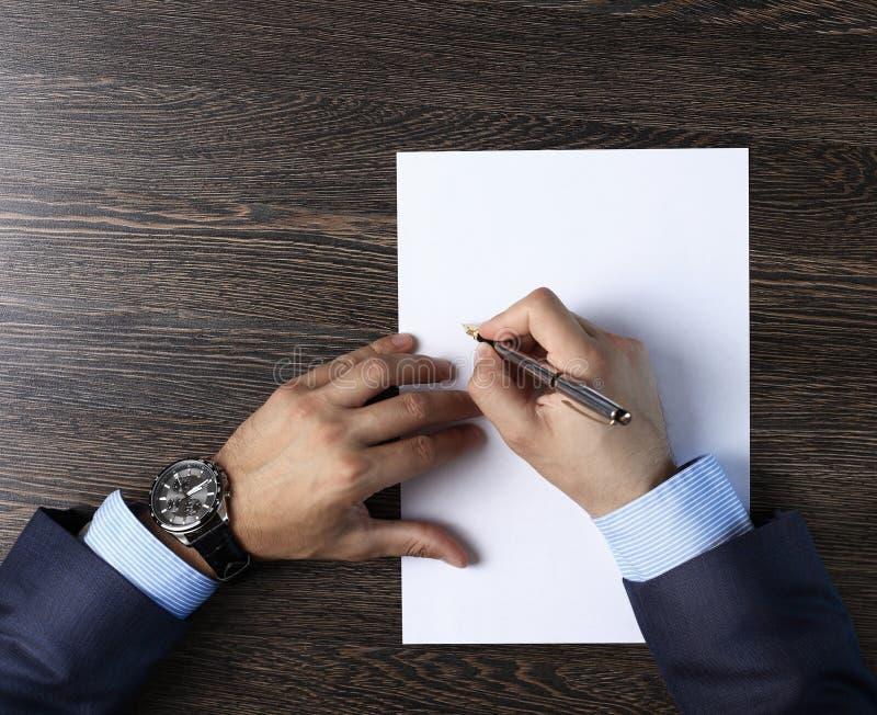 Мужские руки с ручкой над документом стоковое изображение