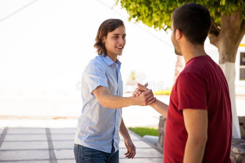 Мужские студенты колледжа приветствуя стоковое фото