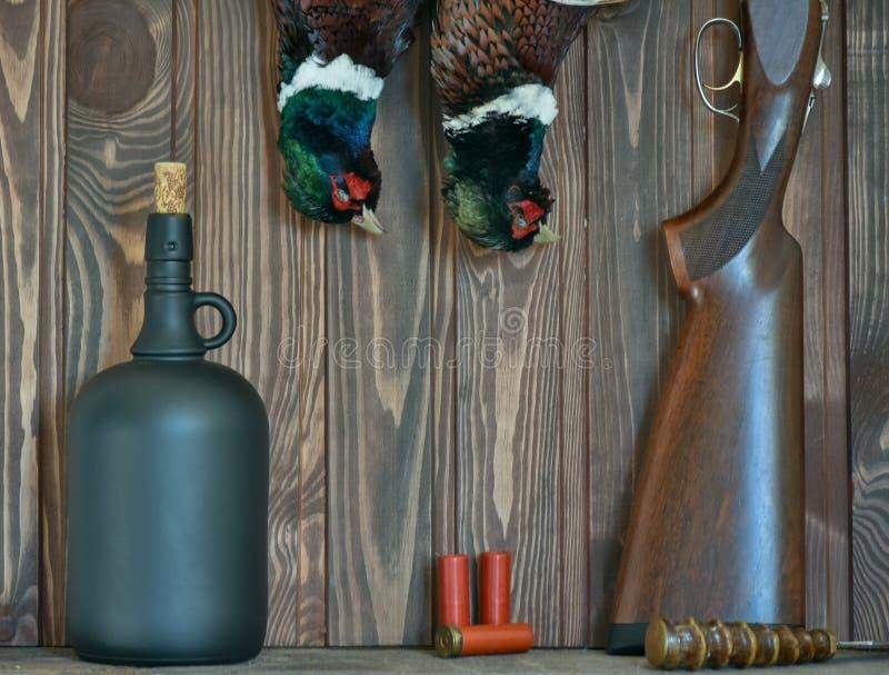 Мужские фазаны, стеклянная бутылка, и оружие, на старой деревянной предпосылке Сезон звероловства стоковое фото