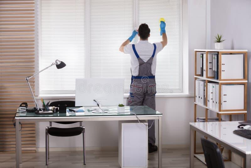 Мужские шторки окна чистки работника с губкой стоковое изображение rf