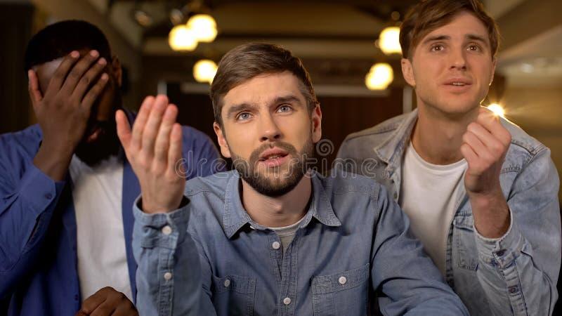 3 мужских вентилятора чувствуя расстроенную потерю игры, наблюдая конкуренцию совместно, отдых стоковое изображение rf