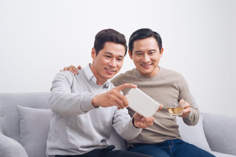 2 мужских друз играя игру на smartphone сидя на софе на h стоковое фото rf