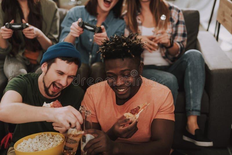 2 мужских друз clinking бутылки пива пока девушки играя видеоигры стоковая фотография