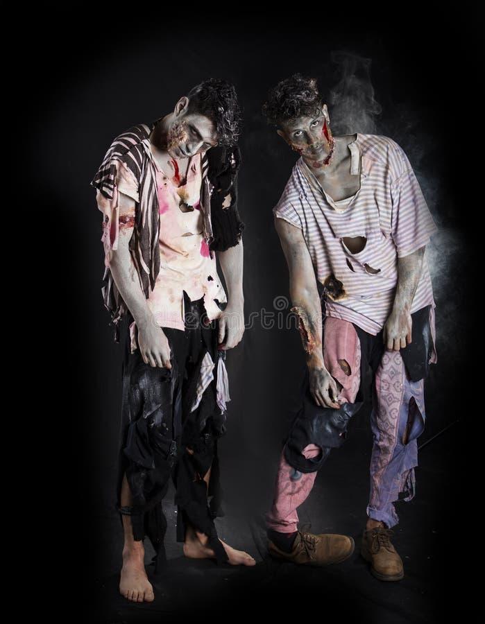 2 мужских зомби стоя на черной предпосылке, во всю длину стоковая фотография rf