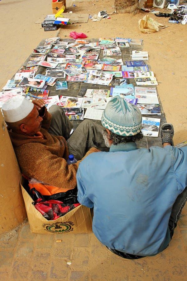 2 мужских поставщика сидя на поле и продавая товары на рынке в Триполи, Libia стоковые фото