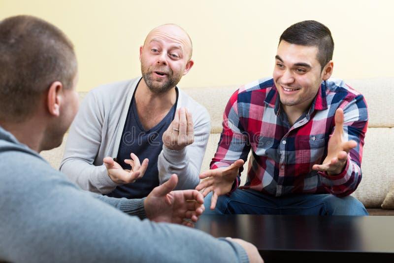 3 мужских друз говоря дома стоковые изображения