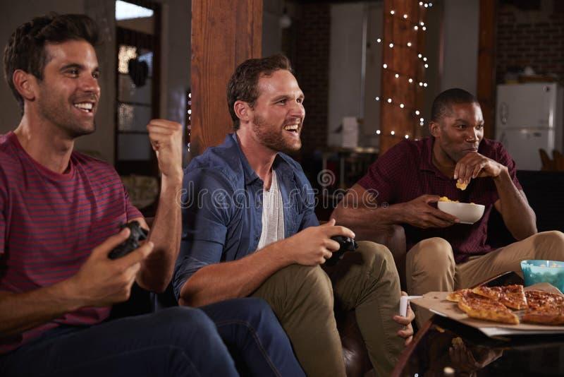3 мужских друз играя видеоигры и есть дома стоковое изображение