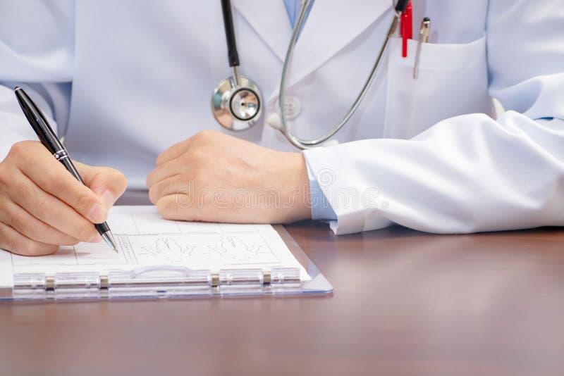 Мужское сочинительство доктора на медицинской форме с стетоскопом близрасположенным стоковое фото rf