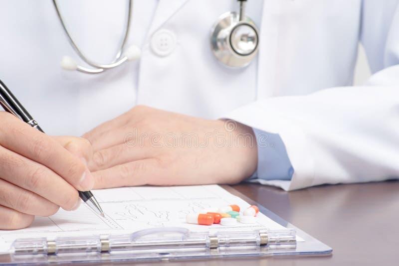 Мужское сочинительство доктора на медицинской форме с стетоскопом близрасположенным стоковое фото