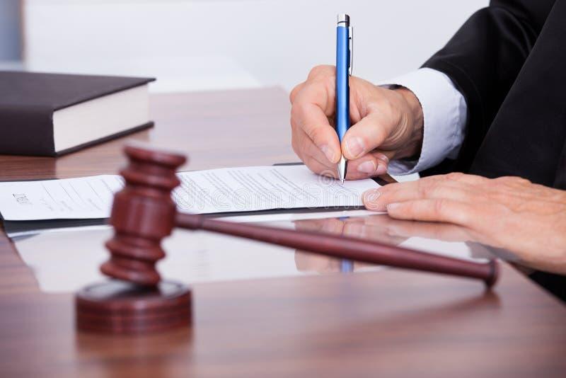 Мужское сочинительство судьи на бумаге стоковое изображение rf
