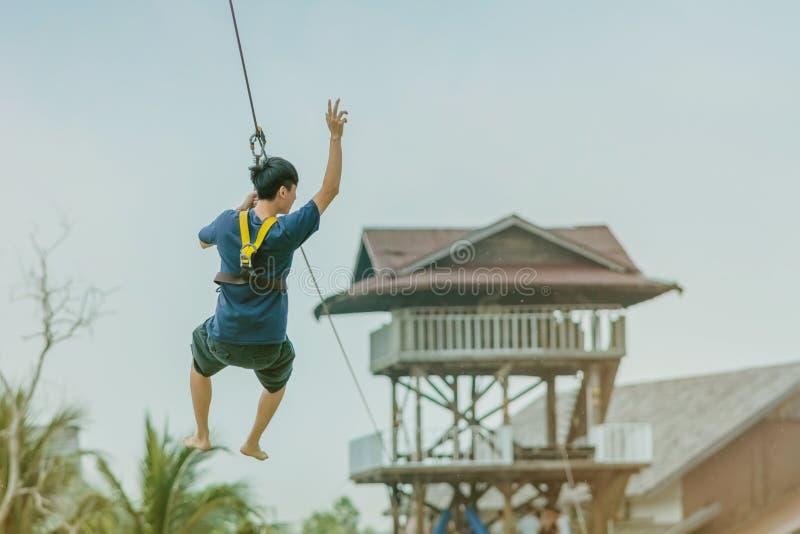 Мужское туристское летание на лисе летания zipline aka через озеро стоковая фотография