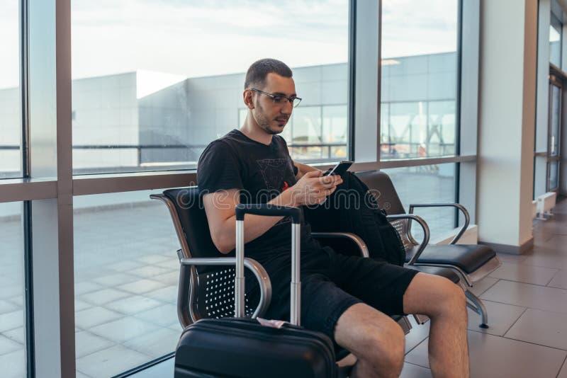 Мужское туристское усаживание на стенде с багажем в зале ожидания в аэропорте стоковое изображение rf