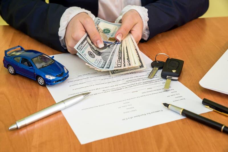 Мужское ` s вручает подписание на форме заявки контракта автомобиля и калькуляторе, долларе стоковые изображения