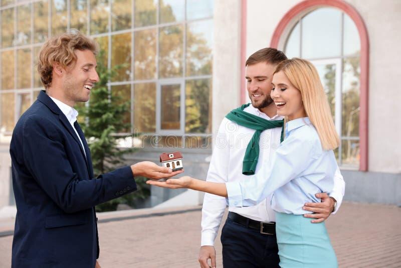 Мужской агент недвижимости давая модель дома для того чтобы соединить стоковое изображение