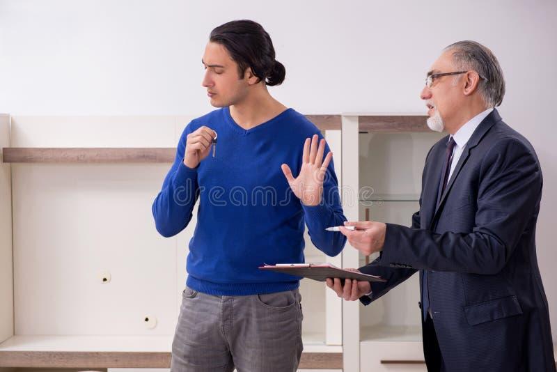 Мужской агент недвижимости и мужской клиент в квартире стоковые изображения rf