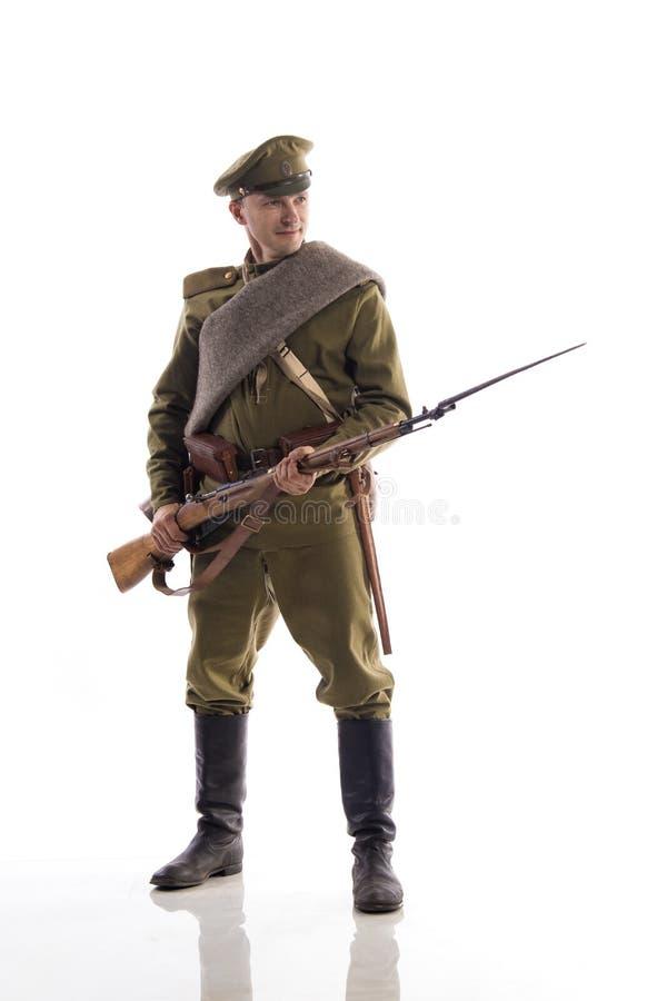 Мужской актер в форме обычного солдата русской армии во время первой мировой войны представляя против белой предпосылки внутри стоковое изображение rf