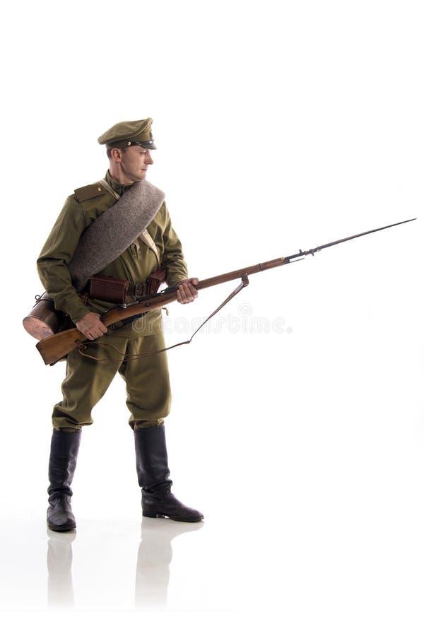 Мужской актер в форме обычного солдата русской армии во время первой мировой войны представляя против белой предпосылки внутри стоковые изображения rf