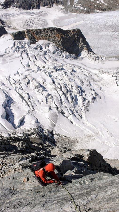 Мужской альпинист на, который подвергли действию взбираясь максимуме трассы над ледником стоковая фотография