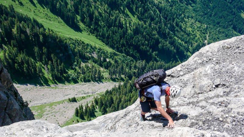 Мужской альпинист на стороне крутой и скалистой горы стоковые фотографии rf
