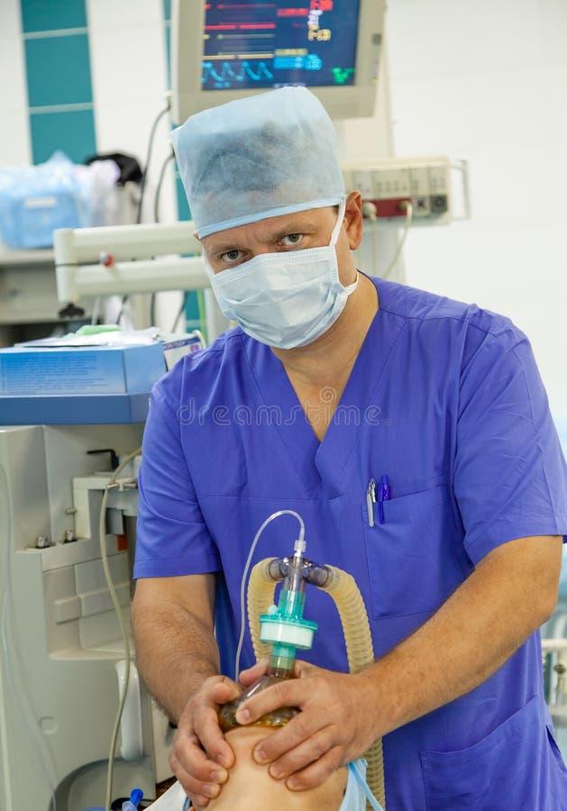 Мужской анестезиолог, работающий в операционной стоковые изображения rf