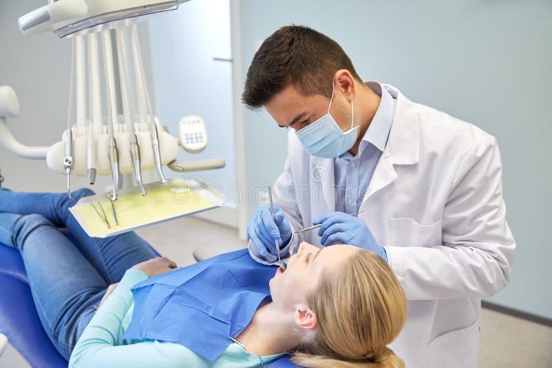 Мужской дантист в маске проверяя женские терпеливые зубы стоковые изображения rf