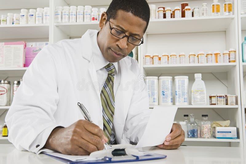 Мужской аптекарь работая в фармации стоковое изображение rf