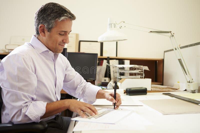 Мужской архитектор работая на столе в офисе стоковая фотография