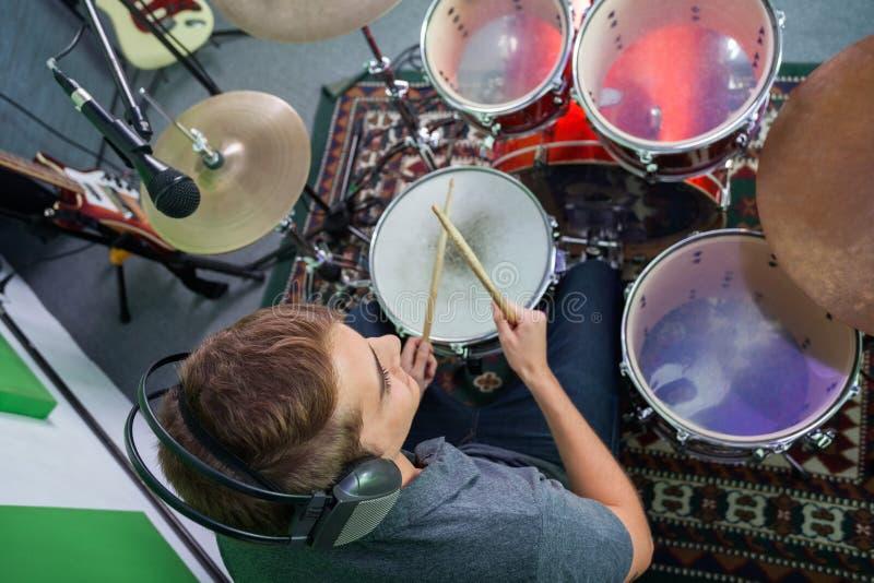 Мужской барабанщик выполняя в студии звукозаписи стоковое фото