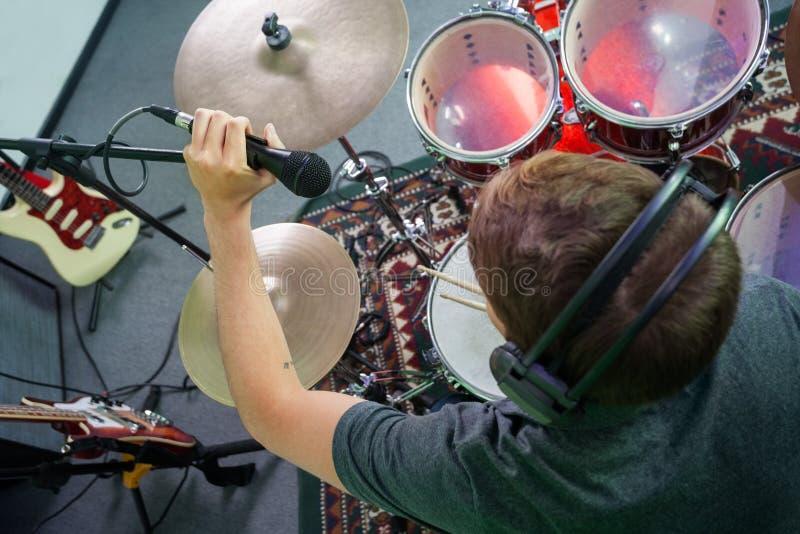 Мужской барабанщик регулируя микрофон в студии звукозаписи стоковая фотография