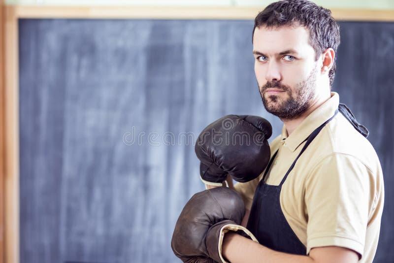 Мужской боксер представляя в черных рисберме и перчатках боксера кожи Брауна стоковое изображение rf
