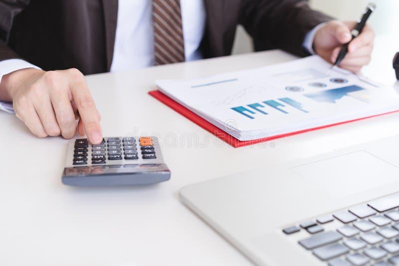 Мужской бухгалтер используя калькулятор и обсуждающ финансовые отчеты стоковое изображение rf