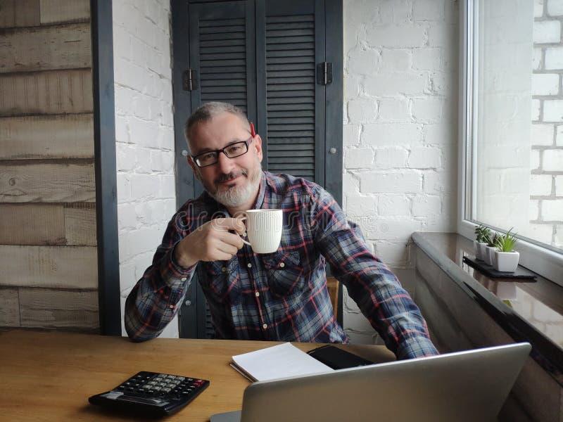 Мужской бухгалтер перед ноутбуком выпивает чай или кофе усмехается стоковое изображение