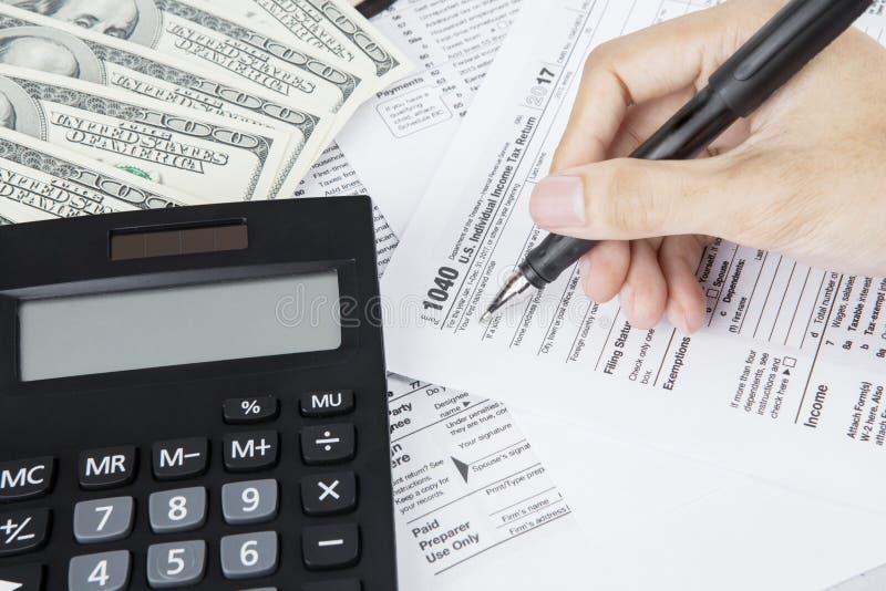 Мужской бухгалтер заполняет вне налоговую форму стоковая фотография
